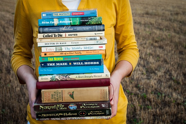 Person holding a large stack of books
