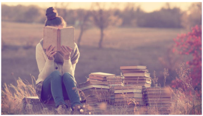 Woman reading a book while sitting on a pile of books outside