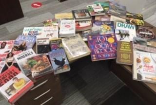 Numerous books laid out on desk