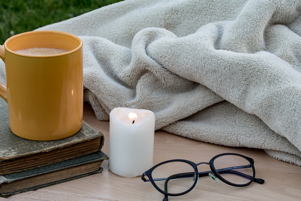 Close up of a candle, reading glasses, a blanket and a mug on two books.