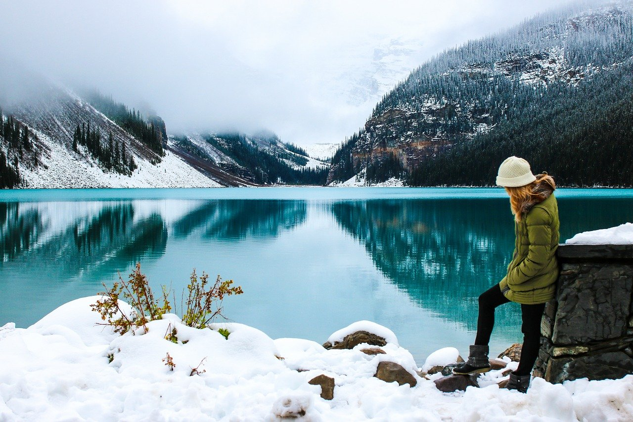 Woman standing by lake with mountain in the background