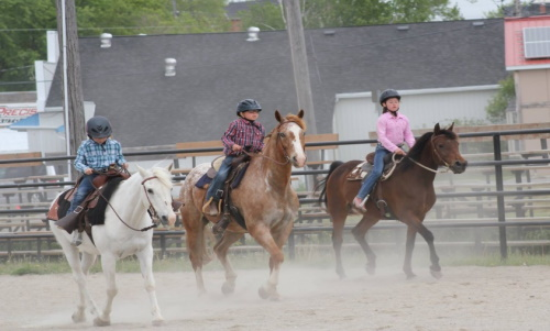 Three girls on horses in the riding ring